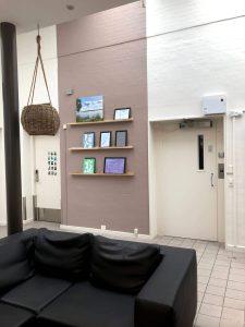 Markering af udstillingsvæg med malet panel. Gallerihylder med klikrammer til nem og dekorativ udstilling af tegninger og malerier